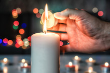 All Saints' Day. Man Lighting A Small Candle From A Big Burning Candle Flame. Prayer And Meditation At Candle Flames. Symbol Of Eternity And Remembrance Of The Dead. Religious Tradition. Bokeh.