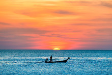 View Of Traditional Fishing Boat In Blue Sea During Beautiful Orange Sunset
