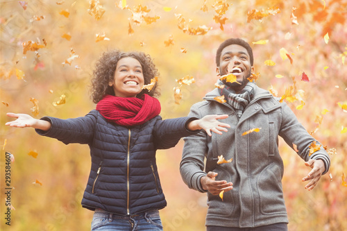 Happy afro couple throwing autumn fall leaves Tableau sur Toile