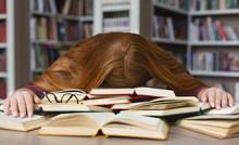Tired Redhead Girl Sleeping On...