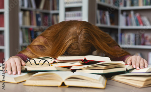 Fotografía  Tired redhead girl sleeping on books at campus library