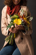 cropped view of woman in trench coat holding bouquet of autumnal wildflowers on black background