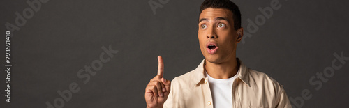 panoramic shot of handsome mixed race man in beige shirt showing idea gesture on Fototapete