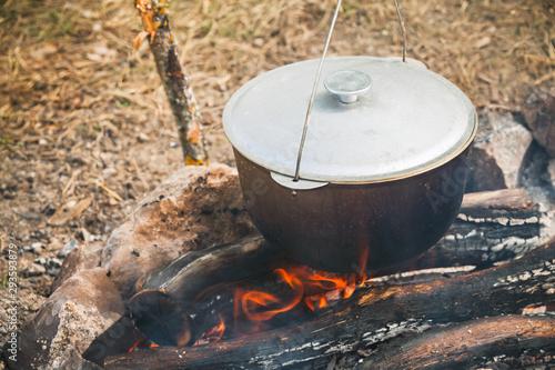 Closed cauldron boiling on a campfire