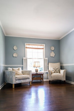Light Blue Sitting Room With Two Cream Colored Chairs And Decorative Plates On The Wall And A Small Accent Table