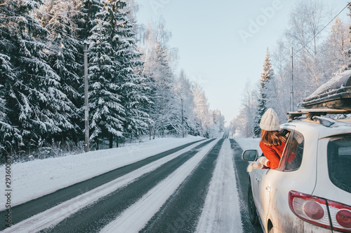Magic car trip on the road by winter forest covered by snow