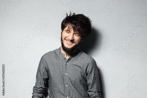 Fotografie, Obraz Portrait of young happy bearded guy with disheveled hair on grey background