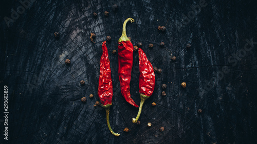 Foto auf AluDibond Hot Chili Peppers Mexican traditional cuisine. Flat lay of three red hot chili peppers on burnt wooden background. Copy space.