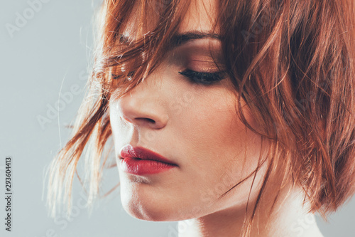 Obraz Professional hair studio. Portrait of woman with styled short red hair, eyes closed. Gray background. - fototapety do salonu