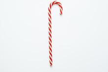 Traditional Christmas Edible Decoration. Flat Lay Of Striped Red Candy Cane Isolated On White Background. Copy Space.