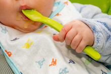 Baby Holds A Spoon And Put It In His Mouth With His Little Hand. Baby First Soilds. Weaning.
