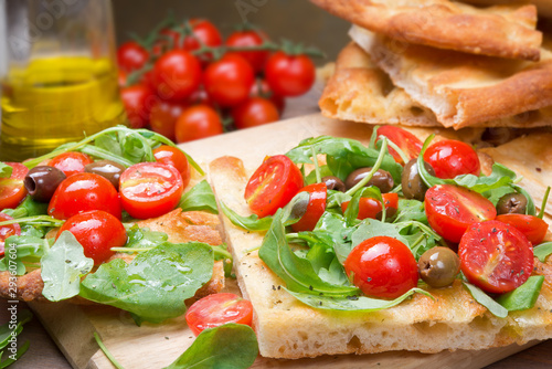 Focaccia, pizza with cherry tomatoes, olives and rocket
