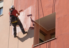 Whitewashing Of A Facade Of A Building Working Suspended With Ropes