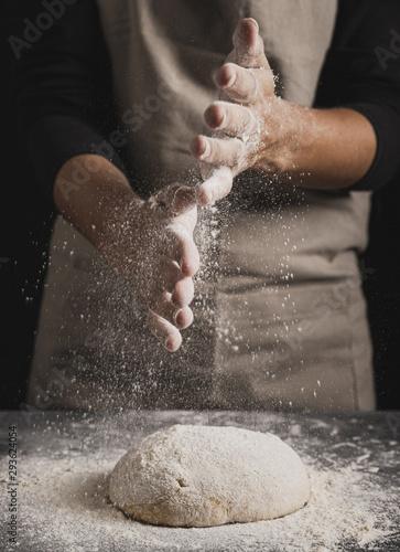 Fotografia  Close-up baker spreading flour on top of dough