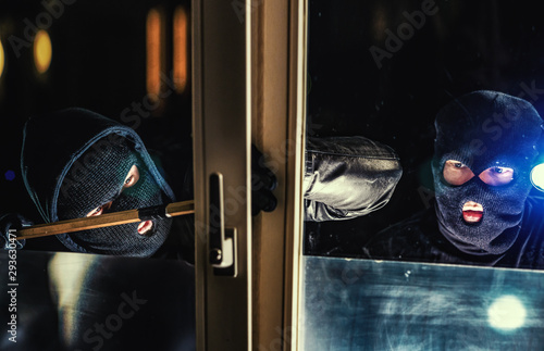 Fotomural  Masked burglar with torch and crowbar breaking and entering into a house - shot