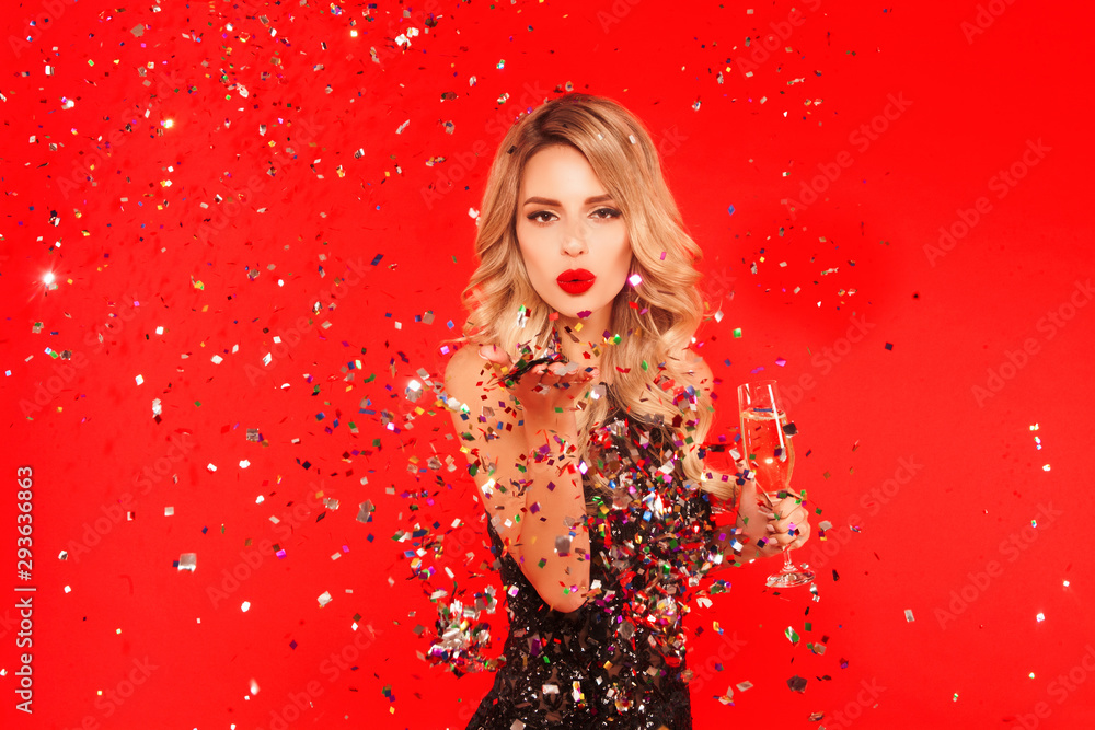 Fototapeta Woman with a glass of champagne celebrating New Year 2020 party. Portrait of beautiful smiling girl in shiny black dress throwing confetti on red background. Free space for text mockup