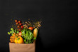 Shopping paper bag full of different fresh vegetables on a black background. Purchases concept. Healthy food organic selection. Top view. Copy space for text.