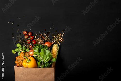 Fototapeta  Shopping paper bag full of different fresh vegetables on a black background