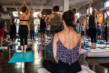 Diverse Group Of People In Yoga Class. A Young Caucasian Woman Is Seen From The Rear, Sitting On An Exercise Mat Inside A Gym, As People Work Through 108 Sun Salutations, With Room For Copy.