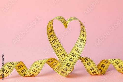 Yellow measuring tape in the shape of a heart on a pink background Fototapeta