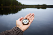 Male Hand Holds A Magnetic Compass Against The Background Of The Forest And A Lake. The Concept Of Finding Yourself The Way And The Truth.