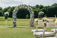 Beautiful Wedding Arch Decorated With White And Pink Rose Flowers On Green Golf Course Outdoors, Copy Space. Wedding Setup. Place For Ceremony. Floral Composition