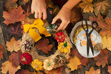 Female Hands Sew A Textile Pumpkin To Decorate An Autumn Straw Wreath On A Wooden Background. DIY Patchwork