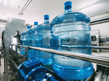 Blue Plastic Bottles With Purified Drinking Water On Automated Conveyor Production Line. Water Factory