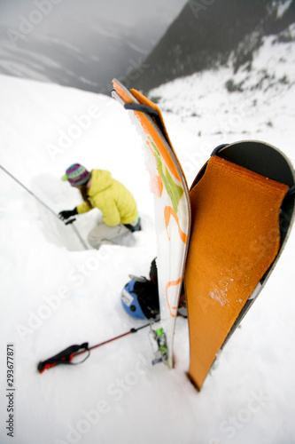 Woman digging a snow pit for avalanche assessment on a trip in British Columbia, Canada.