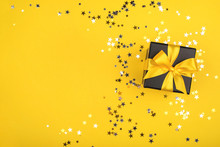 Gift Box On Yellow Background With Sparkling Confetti.