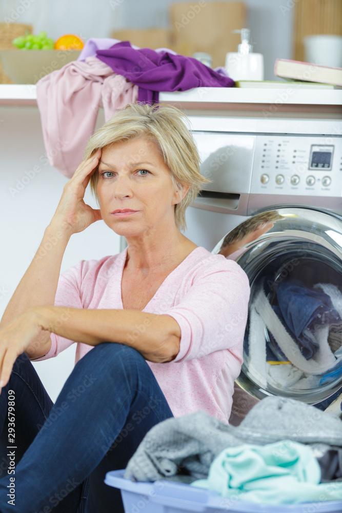 Fototapeta tired mature woman sat by washing machine