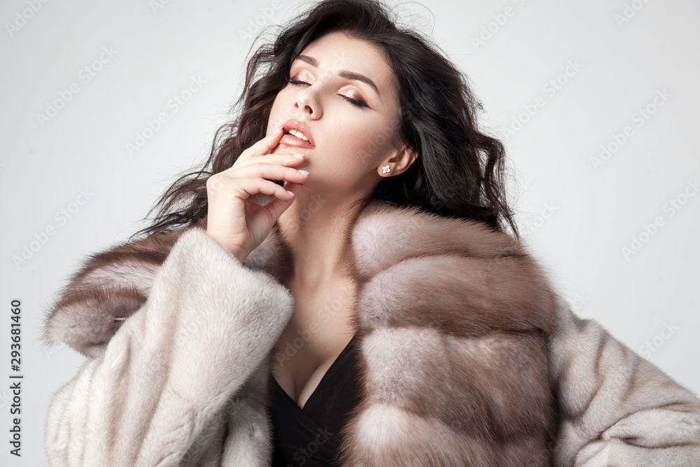 Fototapeta Beautiful elegant woman posing in luxury fashion fur coat over white background. Winter clother.