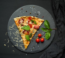 delicious triangular slice of pizza with smoked sausages, mushrooms, tomatoes, cheese and basil leaves