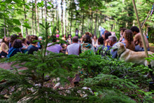 Diverse People Enjoy Spiritual Gathering A Large Group Of People From All Backgrounds Are Seen Sitting Together In A Circle At A Forest Campsite, With A Golden Retriever Dog During A Mindful Retreat.