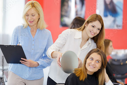 trainee hairdresser showing client their haircut from behind with mirror