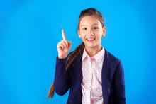 Happy Smiling Primary School Student Girl In Uniform Pointing Her Finger Up Showing Product Looking To Camera On Blue Background