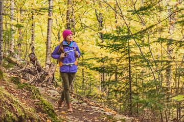 Autumn hike woman walking on forest trail with yellow leaves foliage. Fall outdoor Asian girl hiking with backpack.