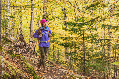 fototapeta na szkło Autumn hike woman walking on forest trail with yellow leaves foliage. Fall outdoor Asian girl hiking with backpack.