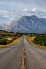 Beautiful View of Scenic Highway with American Rocky Mountain Landscape in the background during a Cloudy Summer Morning. Taken in St Mary, Montana, United States.