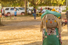 The Scarecrow With A Burlap Face, Green Hat With Overalls Looks At The Camera On The Right Side Of The Pumpkin Patch. An Out Of Focus Background Filled With Warm Sunny Afternoon Has Lots Of People.