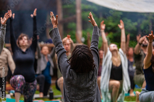 Valokuva Diverse people enjoy spiritual gathering A large group of multigenerational people are seen in a peaceful yoga pose with arms raised in air during a woodland retreat for body and mind