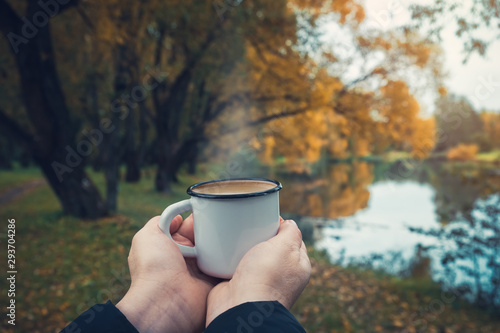 Foto Female hands hold a enameled cup of coffee on autumn landscape outdoors