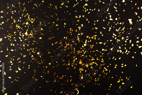 Obraz Gold foil confetti on black background. Flatlay. - fototapety do salonu