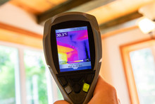 Indoor Damp & Air Quality (IAQ) Testing. A Closeup View Of An Infrared Thermal Vision Device, Pointing Towards The Ceiling And Large Windows Of A Residential Property, Checking For Cold Bridging.