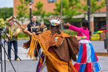 Entertainment At Multicultural Festival. Dancers Are Seen From Behind, Wearing Traditional Costume, With Ribbons And Sacred Objects During A Fusion Of Ancient Music Cultures.