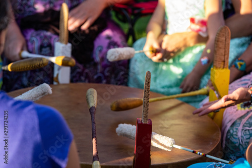 Sacred drums during spiritual singing. A close up view during a traditional singing circle where participants gather round a mother drum and play traditional native music, with copy space. - 293724235
