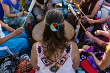 Sacred Drums During Spiritual Singing. A High Angle View Of A Woman Wearing Native Headband And Colorful Clothes During A Singing Circle Of People Around A Sacred Mother Drum Outdoors.