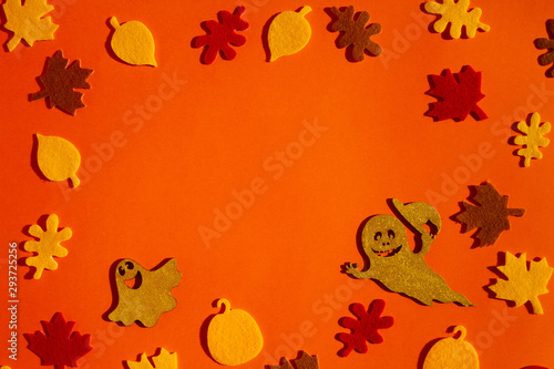 Paper leaves and ghosts for Halloween party are laid out on an orange background.
