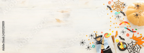 holidays image of Halloween. Pumpkins, bats, treats and cute witch over white wooden background. top view, flat lay. banner