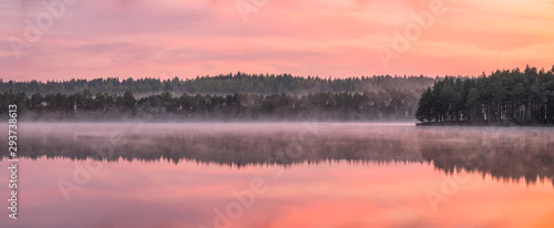 Fototapeta Beautiful sunrise landscape with misty mood and calm lake at foggy summer morning in Finland obraz